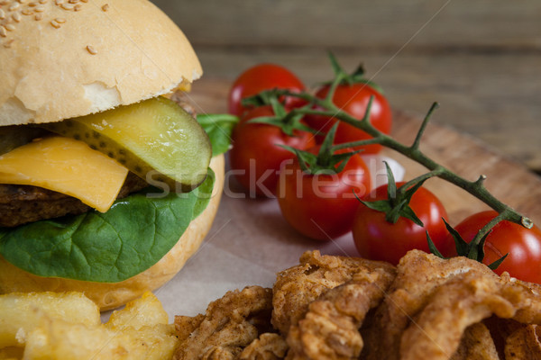 Hamburger, onion ring, cherry tomato and french fries on chopping board Stock photo © wavebreak_media