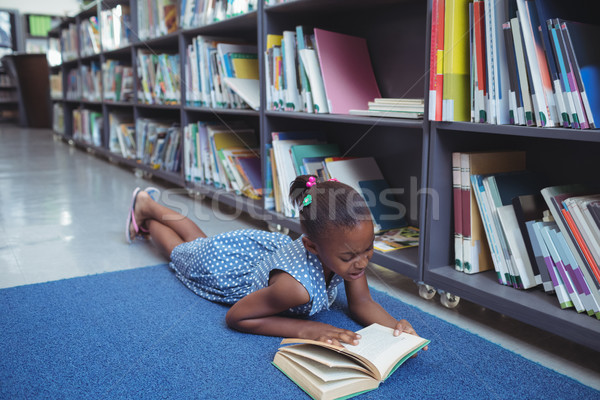 Girl reading book by shelf in library Stock photo © wavebreak_media