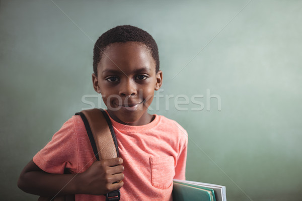 Portrait of boy with backpack and books against greenboard Stock photo © wavebreak_media
