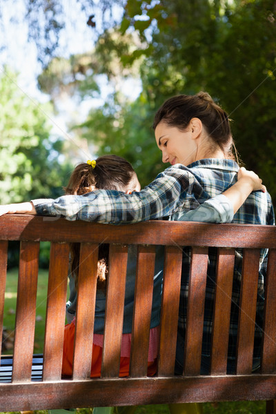 Rear view of mother and daughter sitting with arm around on wooden bench Stock photo © wavebreak_media