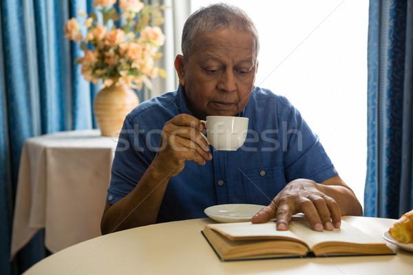 Senior man having drink while reading book in nursing home Stock photo © wavebreak_media