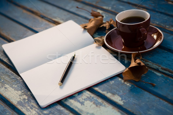 Close up of open book by coffee cup on wooden table Stock photo © wavebreak_media