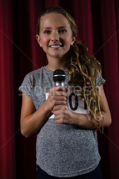Stock fotó: Mosolyog · lány · tart · mikrofon · színpad · színház