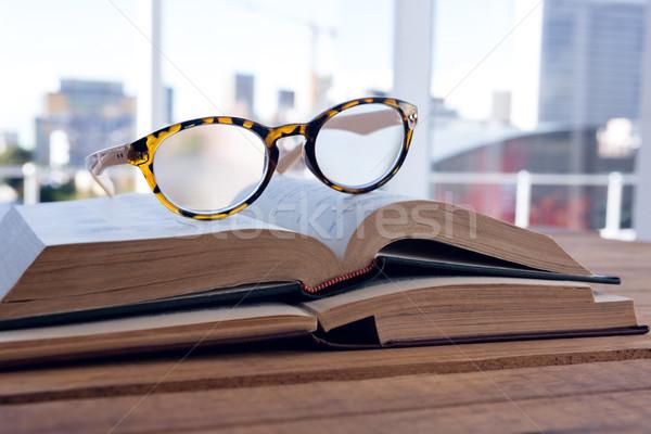 Közelkép szemüveg nyitott könyv asztal könyv fa Stock fotó © wavebreak_media