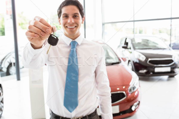 Salesman standing while offering car keys Stock photo © wavebreak_media
