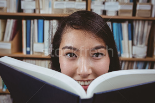 Mosolyog diák rejtőzködik arc mögött könyv Stock fotó © wavebreak_media