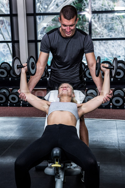 Fit woman doing dumbbells exercise with trainer  Stock photo © wavebreak_media