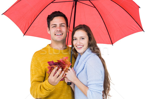 Happy couple under an umbrella holding leaves Stock photo © wavebreak_media