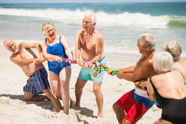 Idősek játszik háború tengerpart napos idő férfi Stock fotó © wavebreak_media