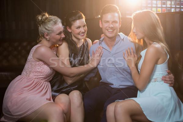 Smiling friends sitting together in sofa Stock photo © wavebreak_media