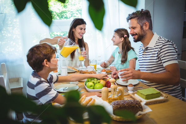 Happy family talking to each other while having breakfast together Stock photo © wavebreak_media
