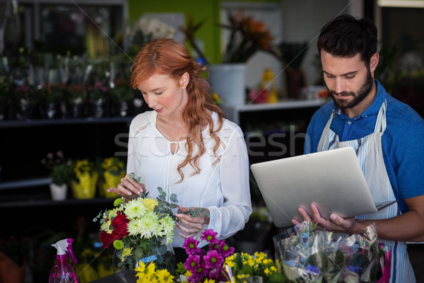 Woman preparing flower bouquet while man using laptop Stock photo © wavebreak_media