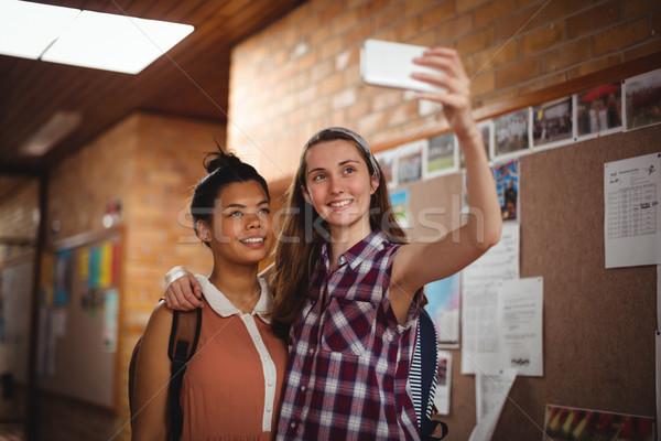 Felice studentesse cellulare corridoio scuola Foto d'archivio © wavebreak_media
