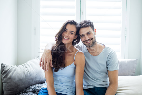 Portrait of couple sitting on bed in bedroom Stock photo © wavebreak_media