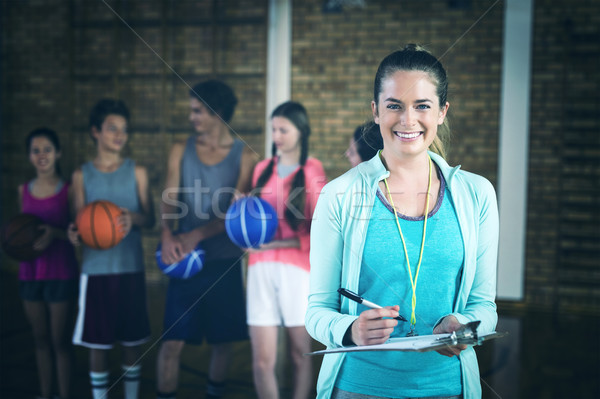 Retrato sonriendo entrenador escrito portapapeles cancha de baloncesto Foto stock © wavebreak_media