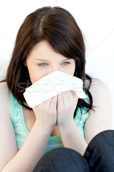 Sick charming woman blowing sitting on a sofa Stock photo © wavebreak_media