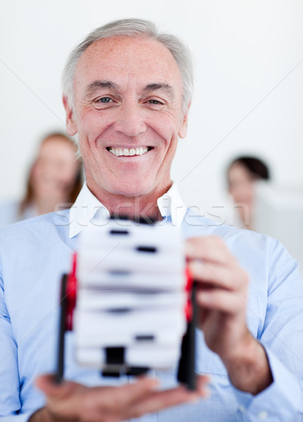 Smiling businessman consulting a business card holder Stock photo © wavebreak_media