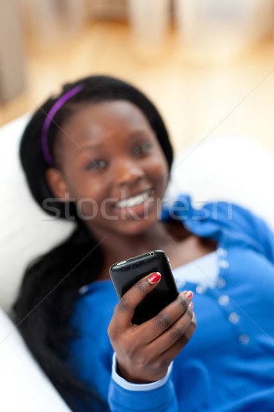 Afro-American woman sending a text lying on a sofa Stock photo © wavebreak_media