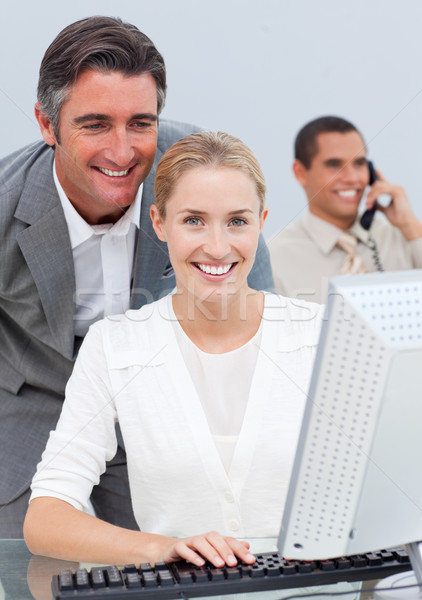 Stock photo: Smiling business team working in the office in a company