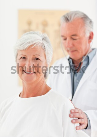Senior woman sitting on a wheelchair talking with her doctor Stock photo © wavebreak_media