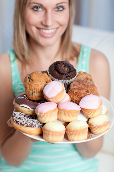 Smiling woman holding a plate of cakes Stock photo © wavebreak_media