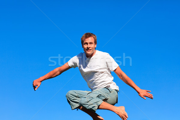 Attractive  Man jumping in the air outdoor against a blue sky background Stock photo © wavebreak_media