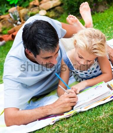 Geconcentreerde blond meisje lezing picknick familie Stockfoto © wavebreak_media
