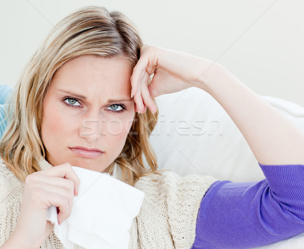 Unhappy sick woman holding tissues looking at the camera sitting on the sofa at home Stock photo © wavebreak_media