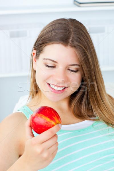 Encantador mujer manzana sesión sofá Foto stock © wavebreak_media