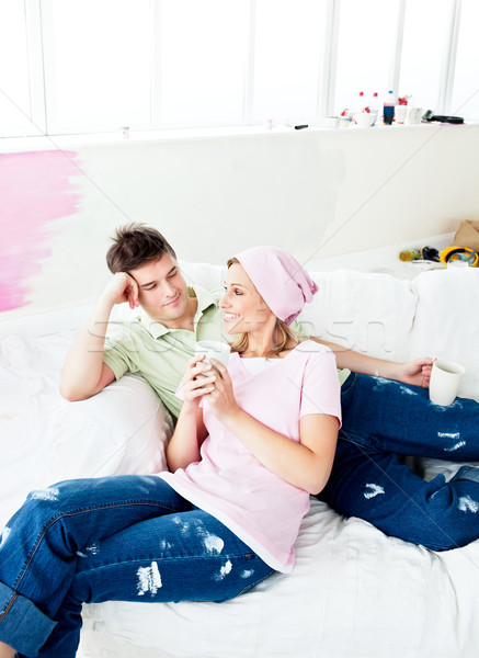 Enamored caucasian couple lying on a sofa after painting a room in their new house Stock photo © wavebreak_media