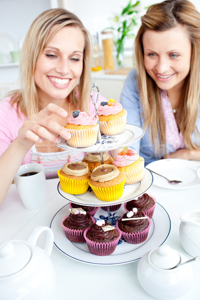 Stock photo: Positive young women eating cakes in the kitchen at home