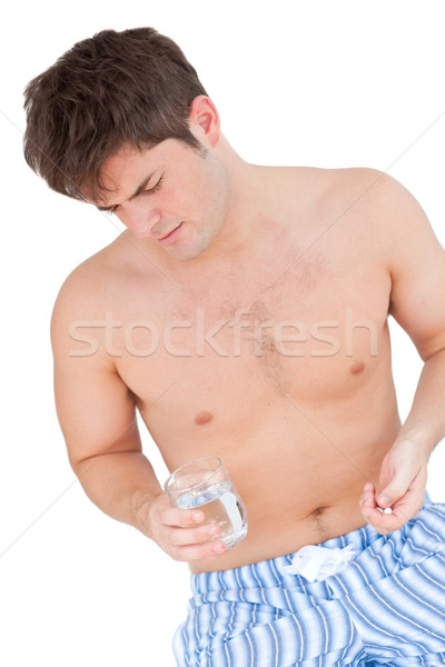 Bare-chested man in pajamas holding pills and a glass of water Stock photo © wavebreak_media