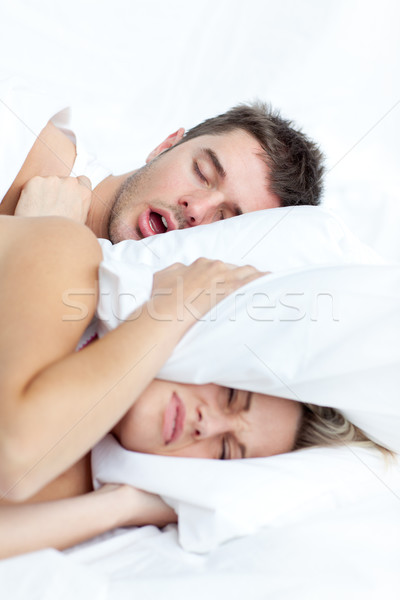 Scenic in bedroom of young couple lying in bed and holding pillow on the ears because of snoring boy Stock photo © wavebreak_media