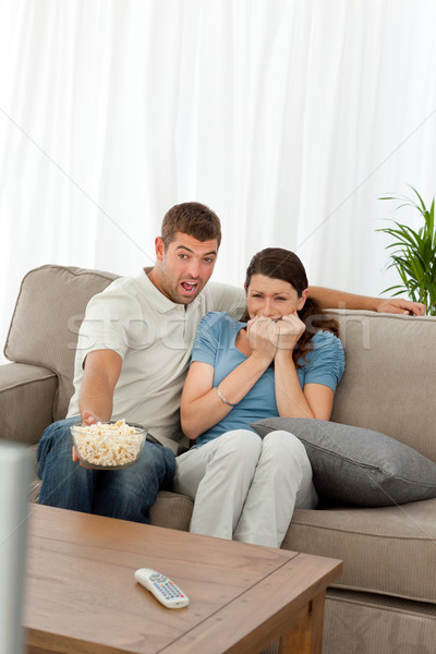 Terrified couple watching a horror movie in the living room at home Stock photo © wavebreak_media