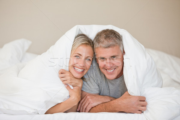 Stock photo: Couple lying down in their bed at home