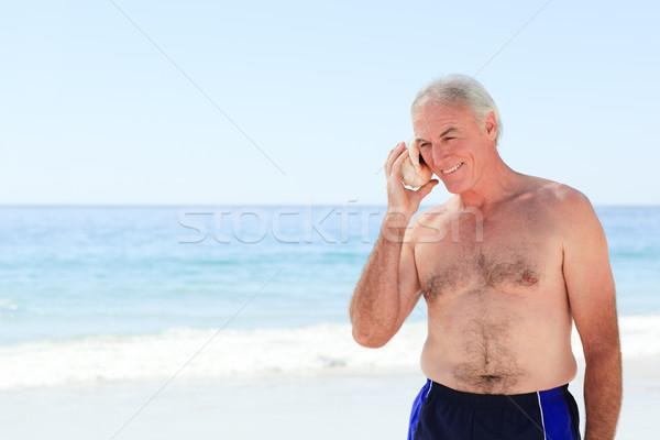 Senior man listening to his shell Stock photo © wavebreak_media