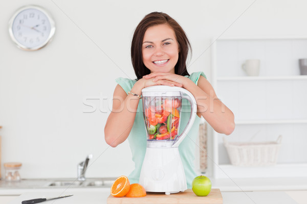 Smiling cute woman posing with a blender while looking at the camera Stock photo © wavebreak_media