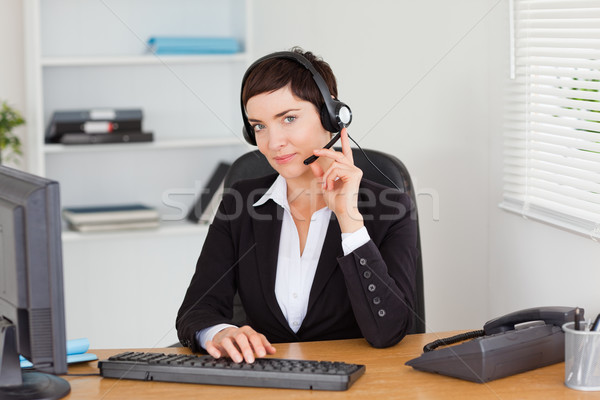 Serious secretary calling with a headset in her office Stock photo © wavebreak_media