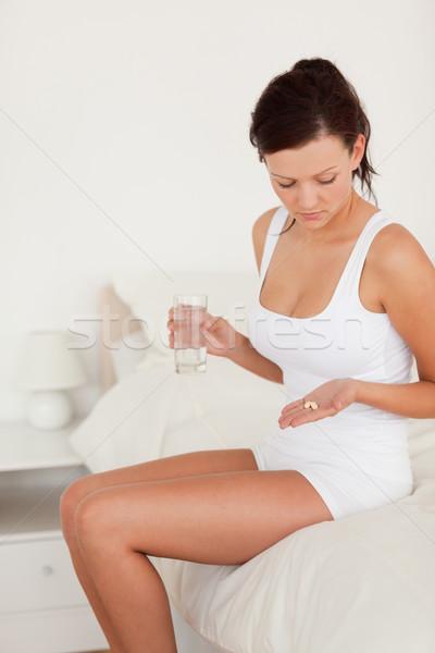 Sick woman holding pills in her bedroom Stock photo © wavebreak_media
