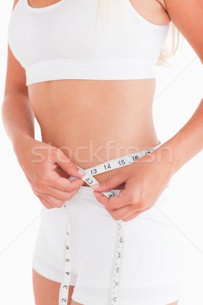 Fit woman measuring her waist in a studio Stock photo © wavebreak_media