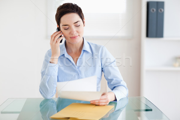 Portrait of a brunette Businesswoman sitting behind a desk with papers on the phone in an office Stock photo © wavebreak_media