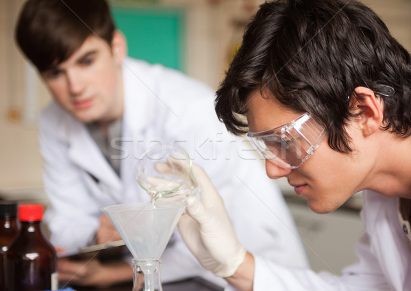 Close up of students in chemistry making an experiment in a laboratory Stock photo © wavebreak_media