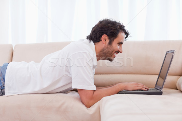 Handsome man using a notebook in his living room Stock photo © wavebreak_media