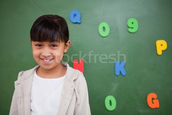 Souriant écolière posant tableau noir classe sourire Photo stock © wavebreak_media