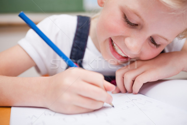 Close up of a schoolgirl writing something in a classroom Stock photo © wavebreak_media