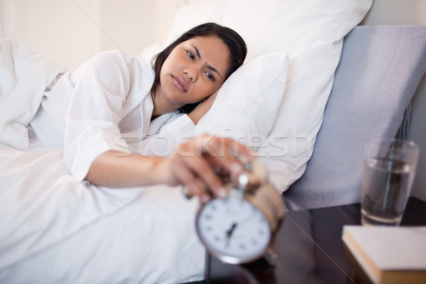 Young woman annoyed by ringing alarm clock Stock photo © wavebreak_media