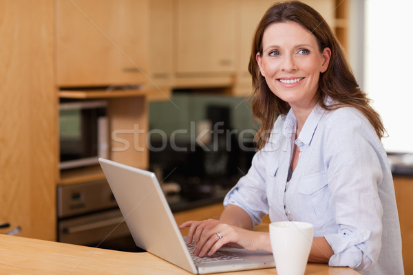 Stock photo: Smiling woman in the kitchen with her notebook