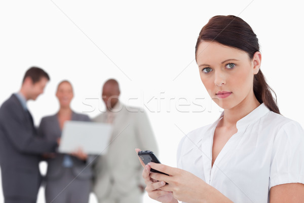Tradeswoman with cellphone and associates behind her against a white background Stock photo © wavebreak_media