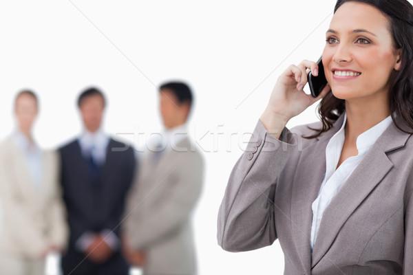 Mosolyog elarusítónő mobiltelefon csapat mögött fehér Stock fotó © wavebreak_media