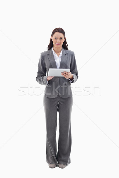 Businesswoman smiling with a touch pad against white background Stock photo © wavebreak_media